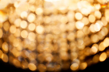 chandelier background: Golden bokeh lights. blurred crystal chandelier background. Darkness and light concept. soft abstract focus photo Stock Photo