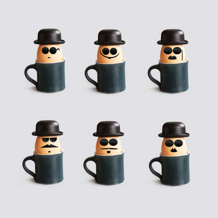bowler hat: Hipster breakfast egg characters with mustache, beard, black bowler hat and glasses. Creative design holiday poster with eggs and cups. Photo with drawn gentleman faces vintage style.