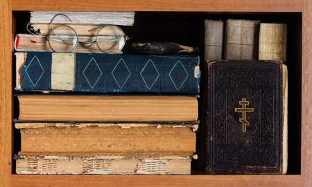 bookish: Library book shelf with Holy Bible book, aged books covers, spectacles. Vintage wooden frame. Christianity conceptual image.