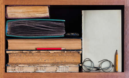 bookish: Still life with wooden book shelf, rare antique books, textured pages, pencils, blank paper scroll and retro design glasses. Path to wisdom concept