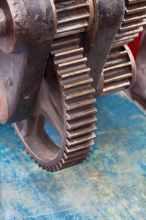 rackwheel: Vintage cogwheel mechanism. Blue paint, shabby wooden background. Retro style industrial technology concept. Soft focus.