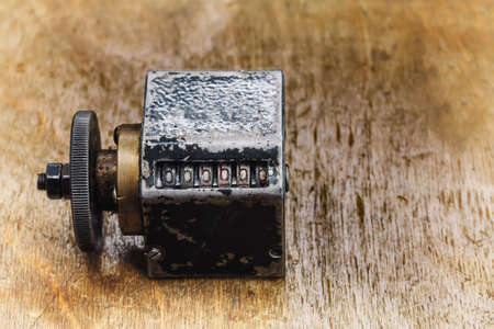 cliche: Vintage cliche stamp with number 666666. aged metal counter mechanism on wooden textured table. Calculation concept. macro view, shallow depth of field