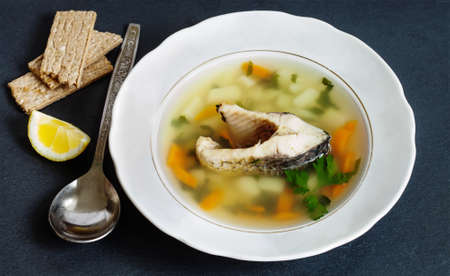 chub: Mediterranean fish food concept. Vintage plate with carp fish soup and vegetables. sliced carp, potatoes, carrot, herbs. copy space