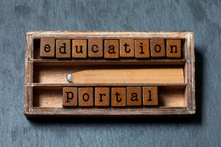 collocation: Education portal conceptual image. Vintage blocks with text, retro style pencil in wooden box. Gray stone background, macro Stock Photo
