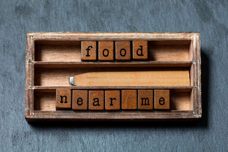 pet store advertising: Food near me. conceptual text. Wooden boxes with letters, retro pencil, aged box background. Gray stone, macro Stock Photo