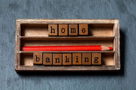 budgeting: Home banking, budgeting concept image. Wooden boxes with letters, red pencil, aged box. Gray stone background, soft focus