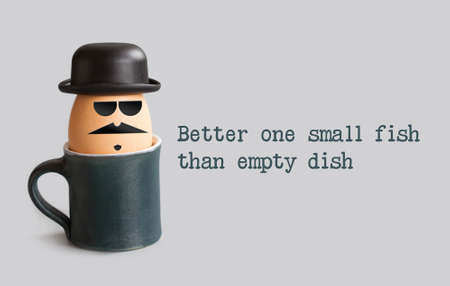 proverbs: Better one small fish than empty dish. Proverbs metaphorical phrase and egg character with drawn gentleman face. Mustache, beard, black bowler hat, glasses.