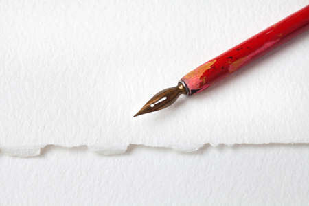 nib: Red nib pen on white paper textured background. macro view fountain pen, shallow depth of field