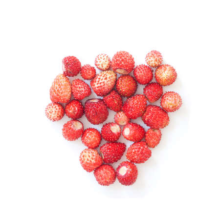 Wild strawberries on white background. Forest red berries formed heart shape.