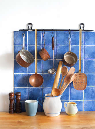 bakelite: Retro design kitchen interior with accessories. Hanging copper kitchenware set. Pot, stewpot, spoon, skimmer, ladle. Different sizes pitchers, cup. wooden table. Blue tiles