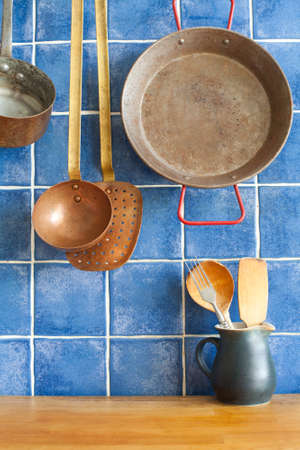 bakelite: Vintage style kitchen accessories. Old utensils pan ladle pitcher with spoon, spatula. Wooden table and blue tile background. Kitchen interior