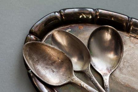 ヴィンテージ食器銀トレイを設定します。古いスタイルのスプーン マクロの表示。灰色の紙背景。