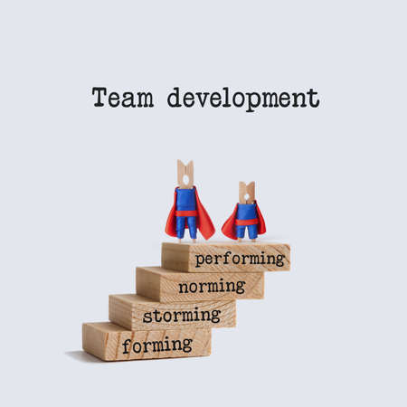 Team development stages. Teamwork concept image with superhero characters on top of the wooden staircase. Words: physiological, safety, love belonging, esteem, self-actualization. Standard-Bild