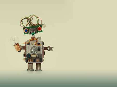Futuristic robot concept with electrical wire hairstyle. Circuits socket chip toy mechanism, funny head, colored eyes, light bulb in hand. Copy space, beige gradient background