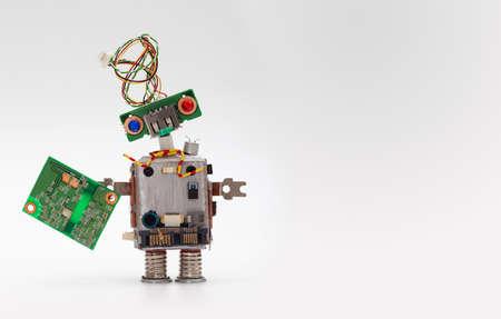 칩 보드와 로봇. 컴퓨터 액세서리 장난감 메커니즘, 재미 머리, 전선 헤어 스타일, 화려한 눈. 복사 공간, 회색 배경