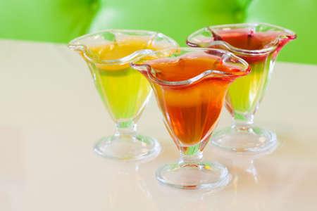 gelatina: jalea rojo amarillo en placa de vidrio, cítricos postre de gelatina fondo beige. enfoque suave