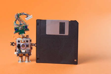 robot with floppy disk. Creative design character blue eyed head, electrical wire hairstyle. Copy space, orange background Stock Photo