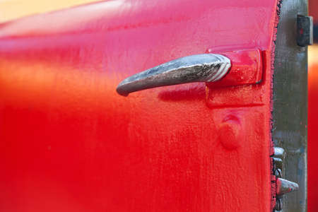 automobile door: Opened red truck door with shabby, chrome handle. automobile accessories detail. selective focus Stock Photo