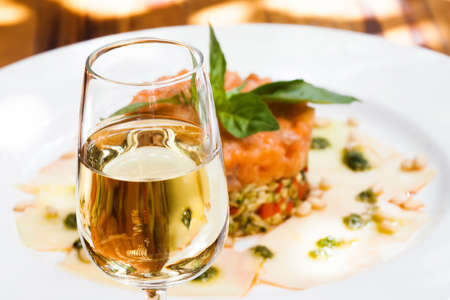 Glass of sherry jerez, pink salmon fish tartar plate background, soft focus photo Foto de archivo