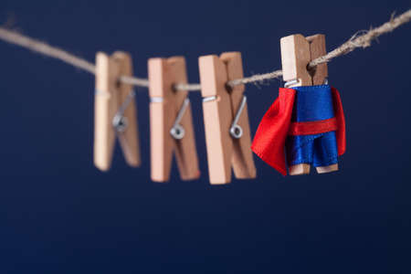 superstar: Powerful super hero conceptual photo with superstar clothespin character in blue suit red cape. leadership and wooden clothespins team at work. Dark blue background.