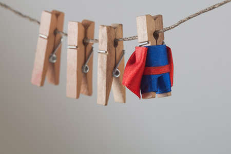 Brave superhero with wooden clothespins team friends. Clothespin leader character in blue suit red cape. gray gradient background. soft focus