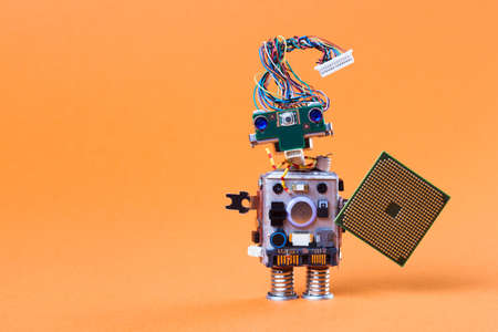 Toy robot with electronic chip board. vintage design toy mechanism with funny head, electrical wire hairstyle, colorful blue eyes. Copy space, orange background