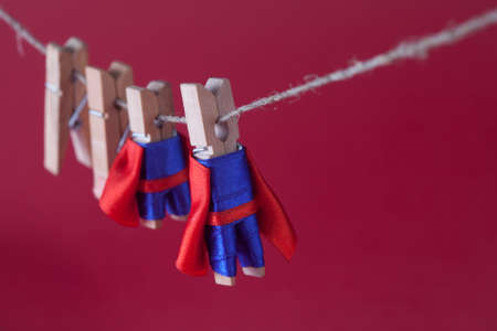 dry suit: Super team leadership concept photo with clothespin superheroes in blue suit and red cape. Big small powerful heroes hanging clothesline. Pink background. macro view