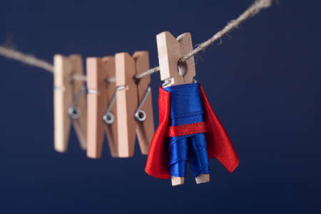 superstar: Powerful superstar clothespin peg character in blue suit red cape. leadership and wooden clothespins team at work. Dark blue background. soft focus. macro