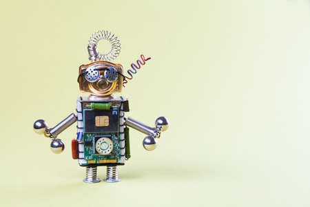 Toy robot with dumbbells. Strength training concept. Circuits socket chip character, funny head, eyes glasses, dumbbells in hands. Copy space, yellow gradient background