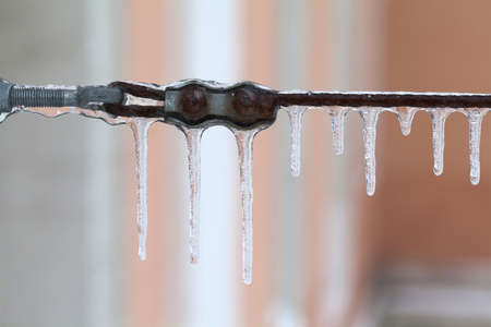 gutter: Frozen metal wire connection. Aged cable icicles. Winter season and cold weather background. macro view, soft focus Stock Photo
