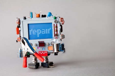 Repair computer service concept. Robot engineer with pliers and light bulb. alert warning message on blue screen monitor head. gray background, shallow depth field. Stock Photo