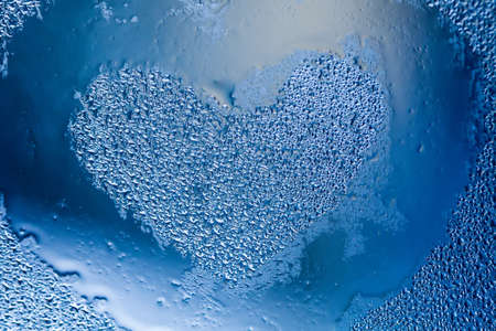 Love heart shape blue color on droplets textured pattern. Abstract window frame with liquid water bubbles. closeup shallow depth of field. Valentines day concept.