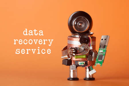 Data recovery service concept. Robotic character with usb flash storage stick. funny toy character black helmet head. orange background, macro view soft focus