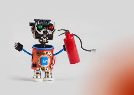 dangerouse: Fire prevention and safety concept. Abstract fireman with light bulb. Plastic head, colored green red eyes, electric wire hands, gears cog wheel and clock parts mechanism. Fun toy character concept. Gradient background, macro copy space Stock Photo