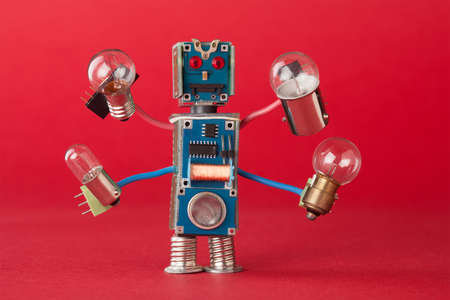 Serviceman illuminator with light bulbs in four hands. Colorful robotic character holds different retro lamps. Funny electronic parts. Red background macro Stock Photo