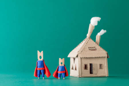 Smart and strong clothespin superheroes and cardboard house. Big small super team characters on green background. soft focus macro view photo
