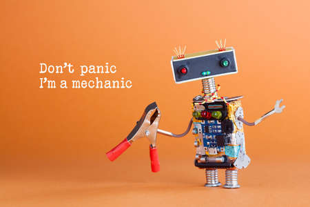 Don't panic I'm a mechanic concept. Toy robot handyman with pliers ready for service work. Fun character colorful head red blue light bulbs eyes. Repairing concept, orange background photo