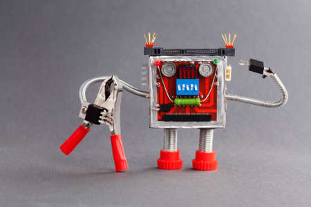 serviceman: Worker ready for job. Serviceman robot character with red pliers. gray background photo Stock Photo