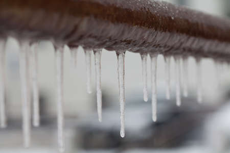 Icicles hanging from a brown pipe. Frozen water and metal surface, winter time concept. selective focus shallow depth of field photo Standard-Bild