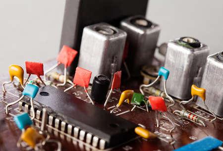 Retro style resistor capacitor macro view, selective focus. Vintage design circuit board. Shallow depth of field