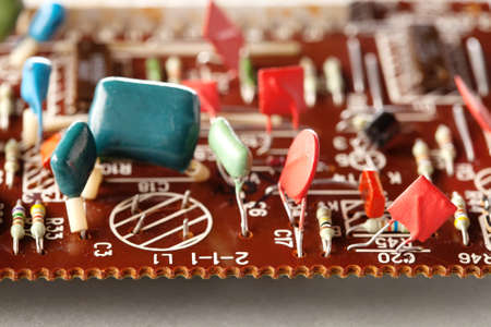 Electronic components vintage design. Selective focus Brown circuit board and soldering capacitors resistors macro view. Shallow depth of field