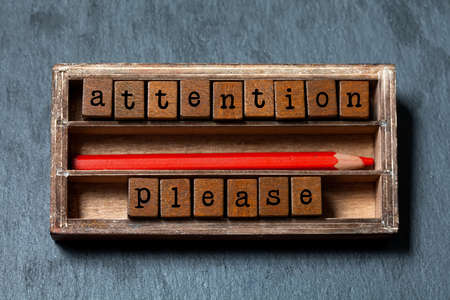Attention please. Warning note and retro style caution banner concept. Vintage box, wooden cubes with old style letters, red pencil. Gray stone textured background. macro, up view, soft focus photo