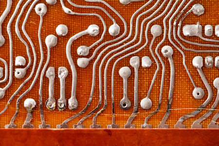 Circuit board background with soldering macro view. Retro technologies concept. Shallow depth field photo