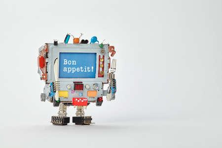 Bon appetit Konzept Roboter-Koch Charakter mit Messer und Gabel in die Arme. Retro-Stil Cyborg Monitor Gesicht, blauen Bildschirm Ihre Mahlzeit wünschen genießen. Grau Papier Hintergrund Kopie Raum.