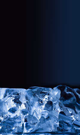 Piece of ice on blue background. Macro view transparent glacial crystal gems objects. Frozen water abstract shapes, soft focus. copy space. Stock Photo