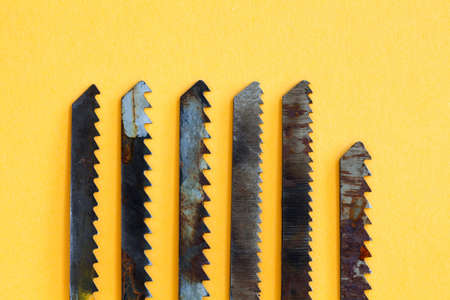 Carpentry saw blade teeth set. Rusty textured woodworking instrument on yellow paper background, shallow depth of field.