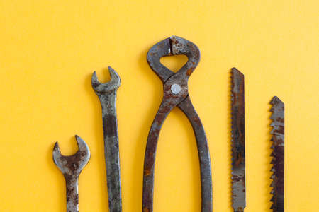 wirecutters: Rusty wrenches pliers saw blades on yellow paper. Vintage iron hand tools instrument for service and repair works Stock Photo