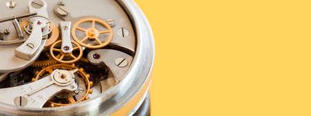 Vintage stopwatch chronometer mechanism macro view, yellow background. Selective focus photo. Copy space photo