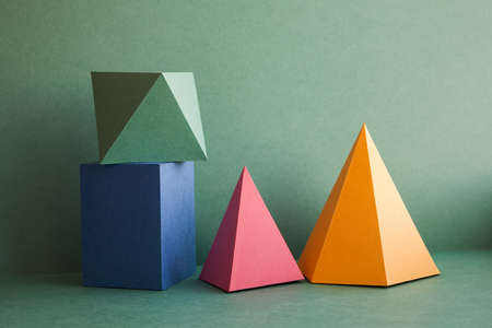 Abstract geometrical solid figures still life. Colorful three-dimensional pyramid prism rectangular cube arranged on green background. Yellow blue pink malachite colored objects textured paper surface. Banque d'images