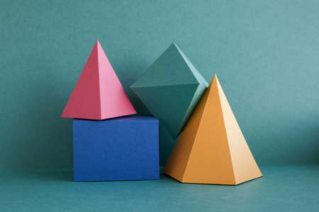 Colorful abstract geometric background with three-dimensional solid figures. Pyramid prism rectangular cube arranged on green paper. Yellow blue pink malachite colored geometrical shapes. Soft focus photo